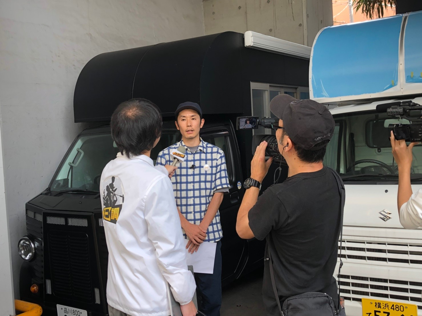 モデルキッチンカーの前でインタビューを受ける代表の浅葉